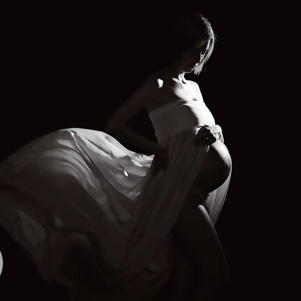 spotlit woman in white dress